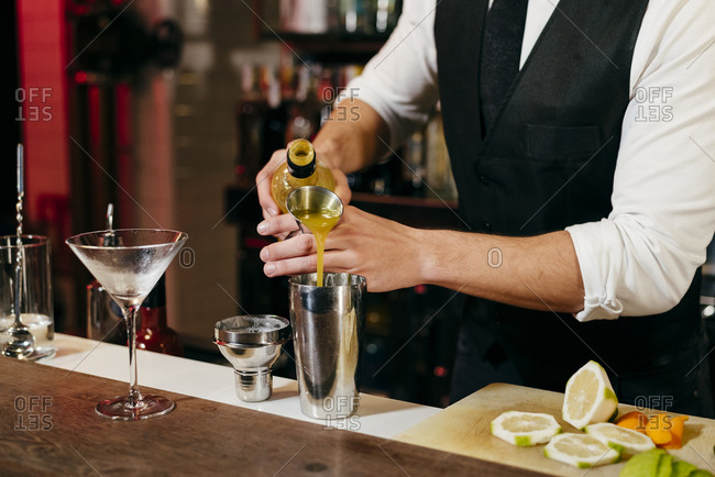 Crop anonymous young elegant barman working behind a bar counter mixing drinks with fruits