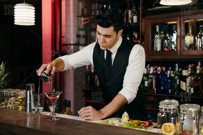 Young elegant barman working behind a bar counter pouring drink from shaker to a glass