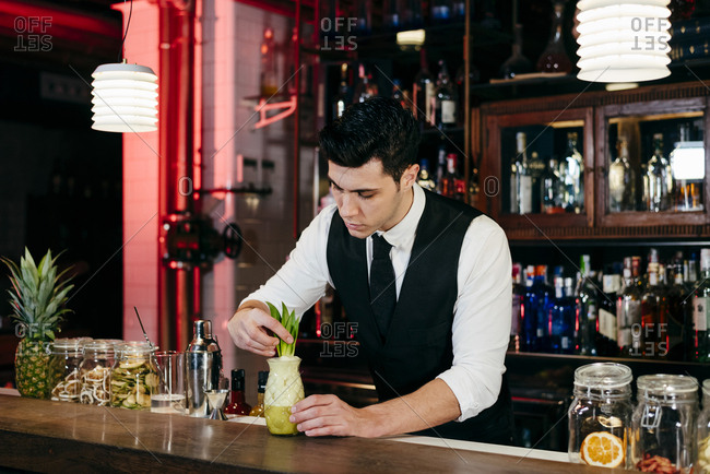 Young elegant barman working behind a bar counter preparing drink in a glass