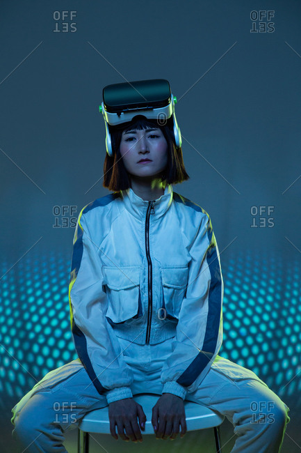 Young woman with virtual reality goggles in forehead while sitting in a chair looking at camera with neon light