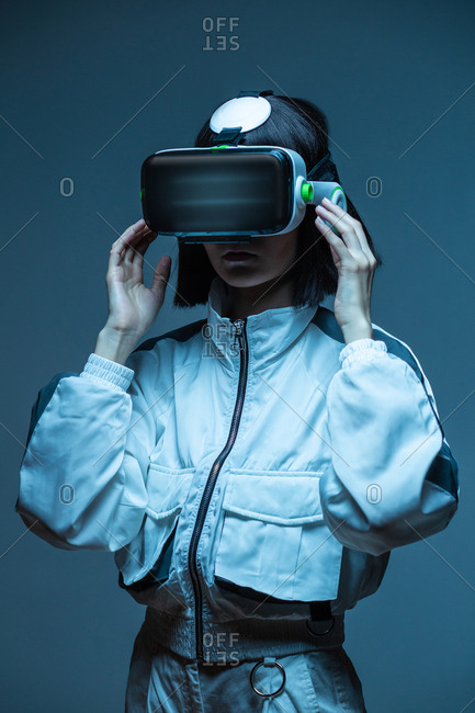 Excited young woman having virtual reality experience in neon light