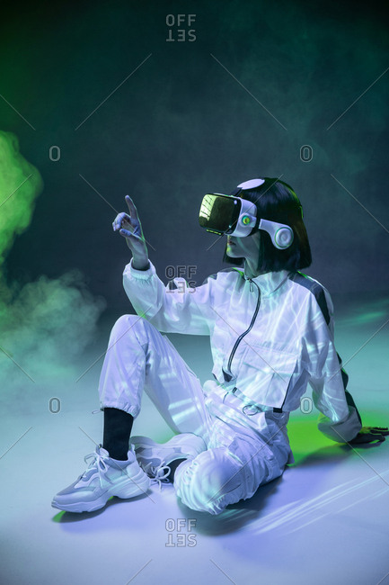 Excited young woman touching air while having virtual reality experience in neon light