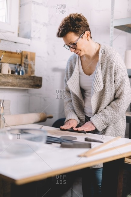 Female potter using clay strips to shape pot on workbench in professional workshop
