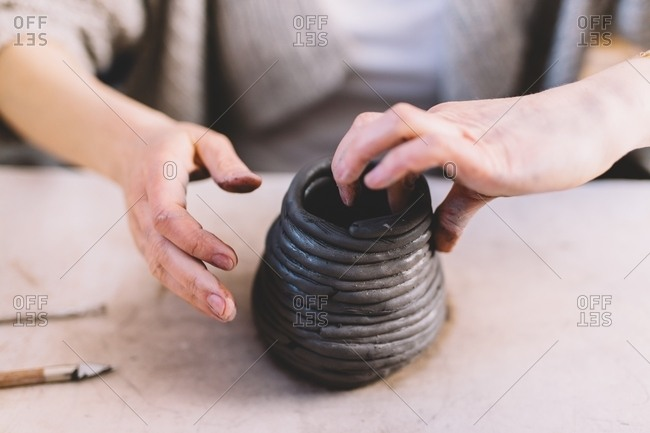 Hands of anonymous female potter shaping vase from soft clay rolls on table