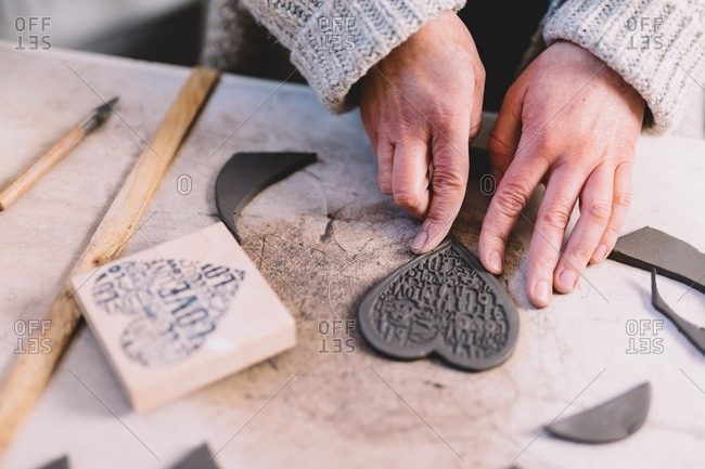 Hands on anonymous woman making ornamental hearts from soft clay on table in potter workshop