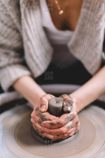 Anonymous female potter with dirty hands making clay pot on wheel in workshop