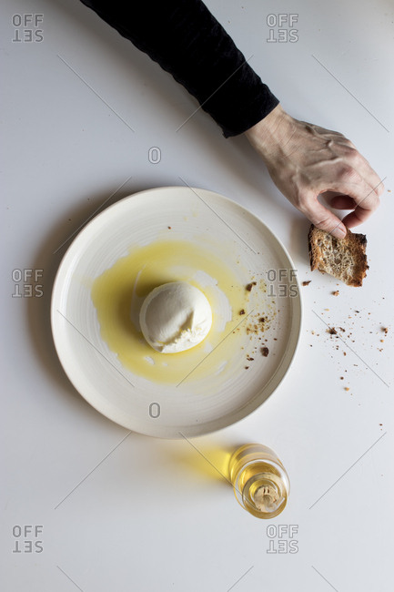 Hands of anonymous elderly person holding green napkin near plate with tasty burrata and piece of bread with oil on white background