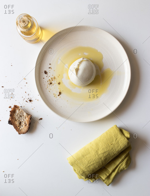 Plate with tasty burrata and piece of bread with oil on white background