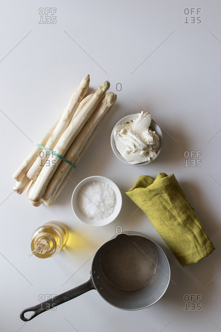 Empty saucepan and green napkin placed on white table near bunch of fresh asparagus and cream with oil and salt