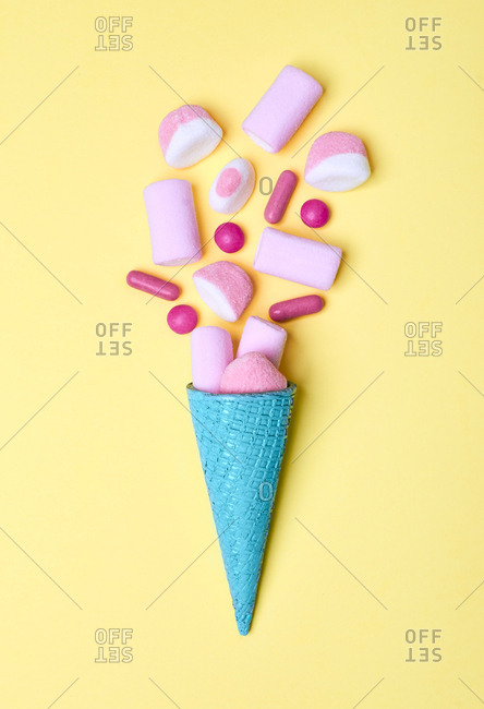 From above of arranged bright blue ice-cream waffle cone with heap of pink candies and marshmallow on yellow background