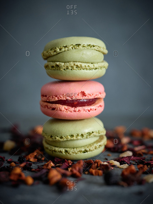pile of bright fresh tasty macaron biscuits on grey board and dry fruits