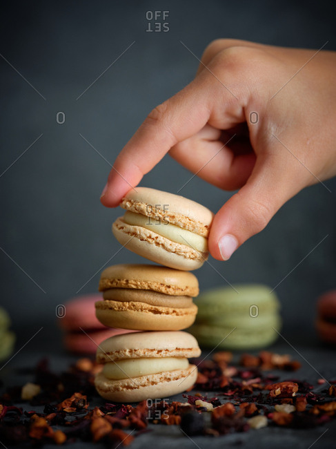 hand of anonymous person taking a macaron from a pile