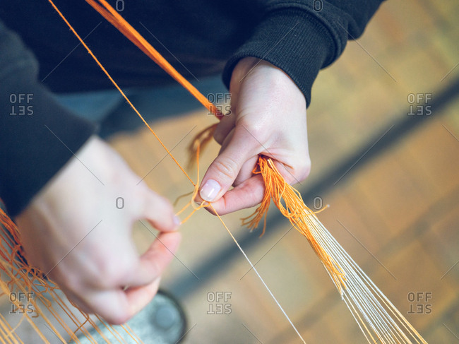 Crop person holding threads on loom