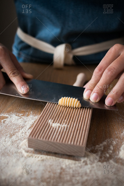 Anonymous female preparing dough for homemade gnocchetti pasta on a wooden tool in table in kitchen