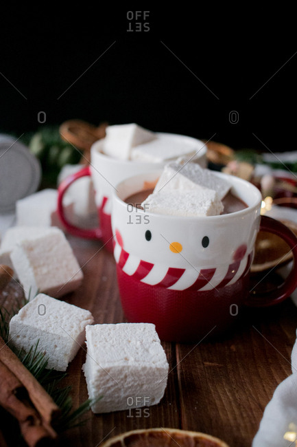 Aromatic cinnamon sticks and dried citruses placed on lumber tabletop near cups of tasty hot chocolate with soft marshmallows and various Christmas decorations