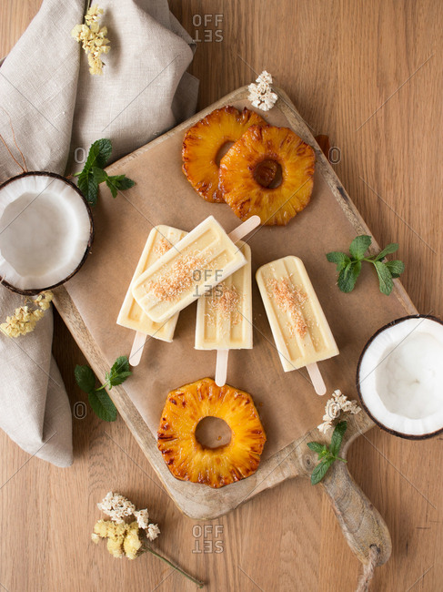 Slices of fresh pineapple and halves of ripe coconut with mint placed around delicious ice cream on board near napkin against wooden tabletop
