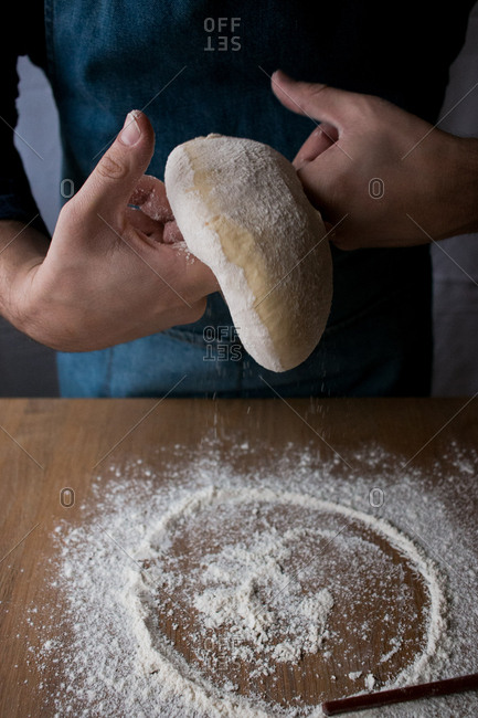 Unrecognizable cook shaping fresh dough with flour while cooking Rosca de Reyes over wooden table in kitchen