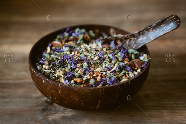 Closeup small wooden bowl filled with aromatic flowers in mix for brewing tea