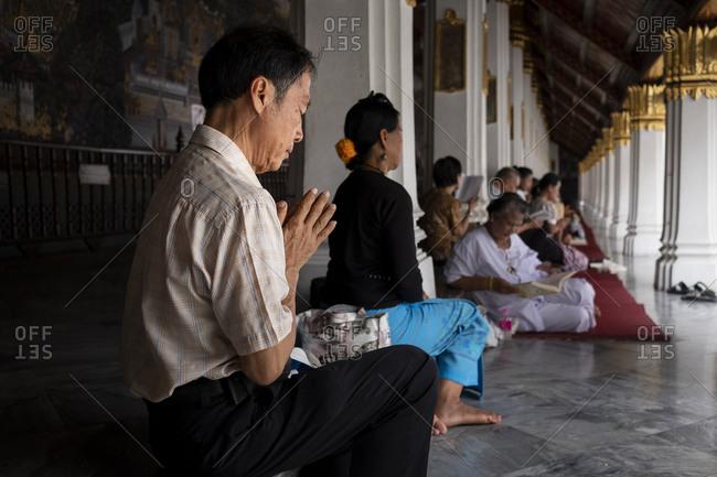 Bangkok, Thailand - September 3, 2018: Man praying at Grand Palace