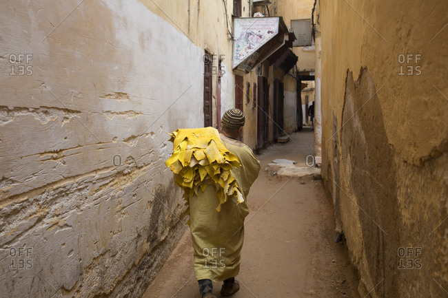 Fes, Morocco - April 6, 2019: Leather worker carrying goats skins down laneway to leather maker