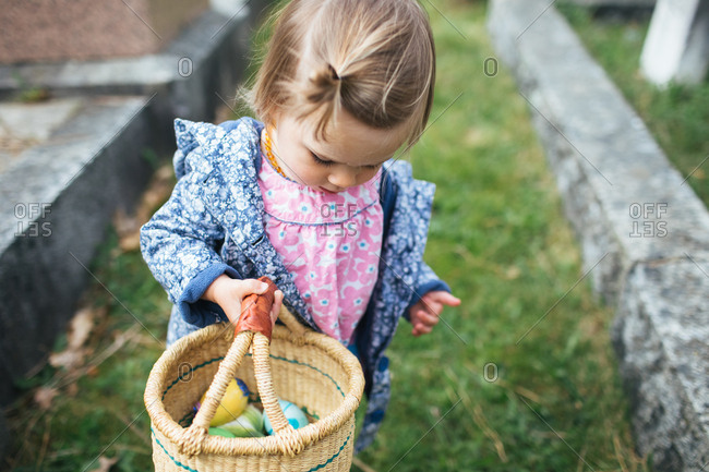 Toddler girl carrying an easter egg basket in a cemetery
