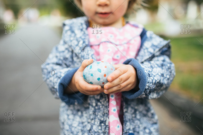 Close up of toddler girl holding a decorated hard-boiled egg