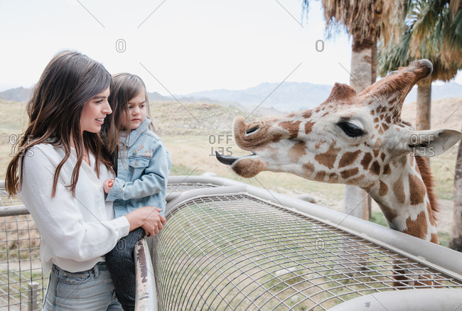 Mom and daughter looking face to face with a giraffe