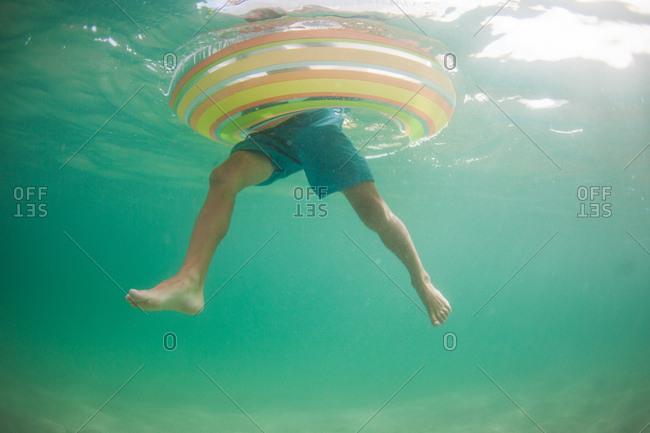Underwater view of boy swimming in an inner tube in the ocean