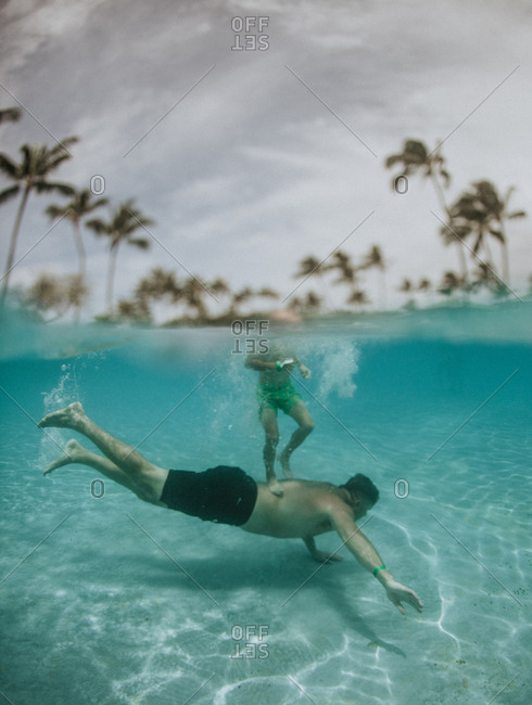 Underwater view of boy riding on dads back in Hawaii