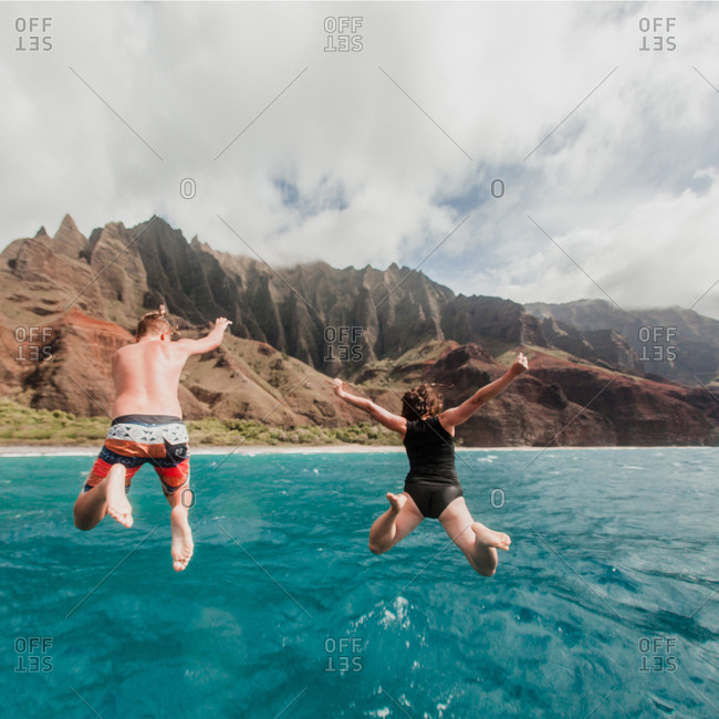 Mom and son jumping off a boat into the ocean on Napali Coast in Hawaii