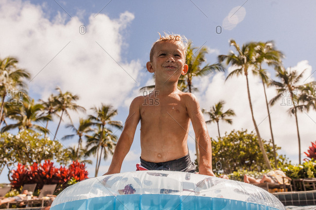 Boy spitting water out in the pool with palm trees behind him in Hawaii