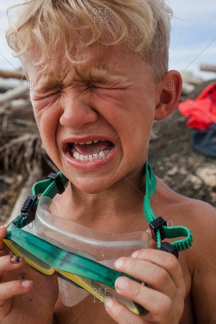 Boy crying with goggles in Hawaii