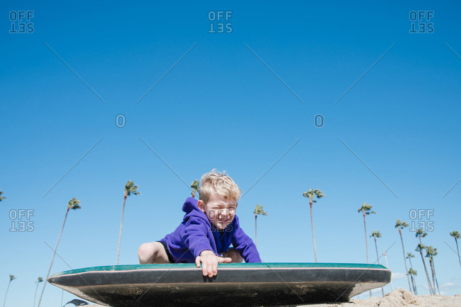Boy with a body board on the sand winking