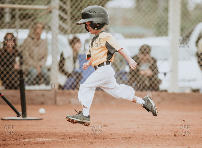 Little boy running to home plate during baseball game
