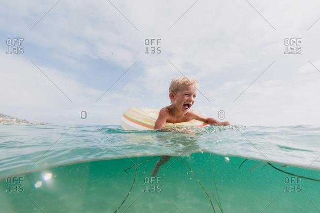 Little boy swimming in an inner tube in the ocean