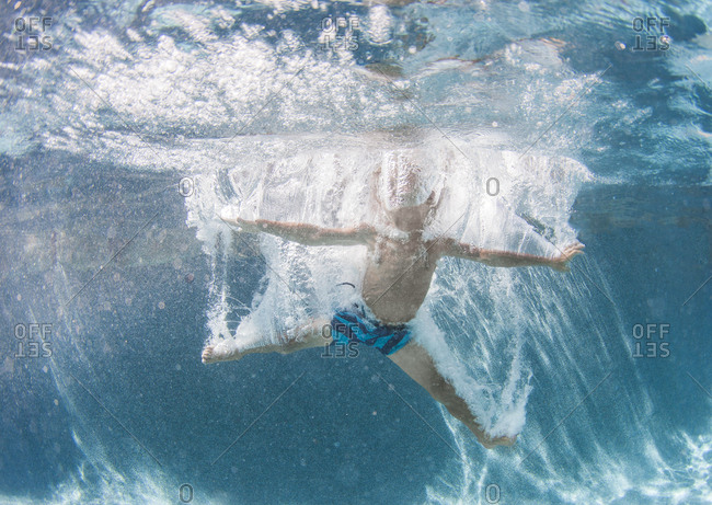 Little boy diving underwater in a pool