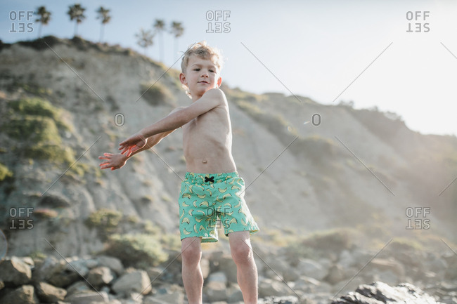 Young boy dancing on a rock at the beach in California