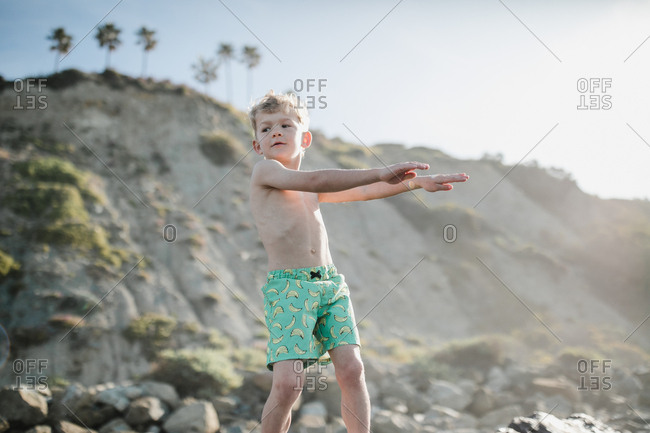 Young boy dancing the floss at the beach