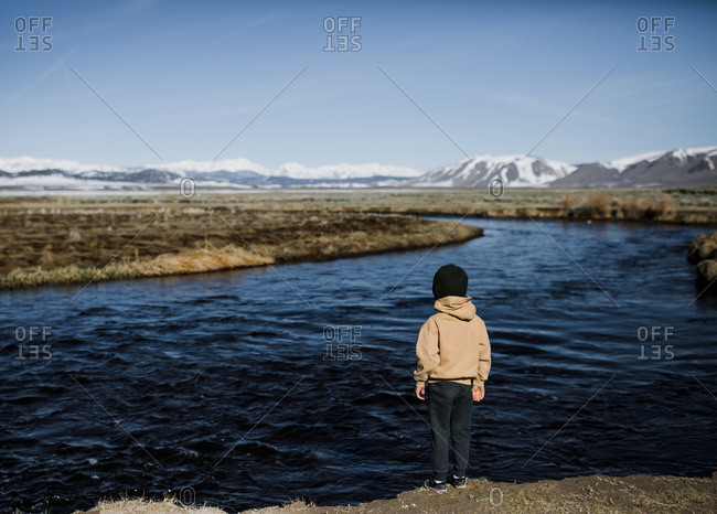 Young boy looking out at river with mountains in the background