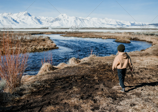 Young boy walking by river with mountains in the background
