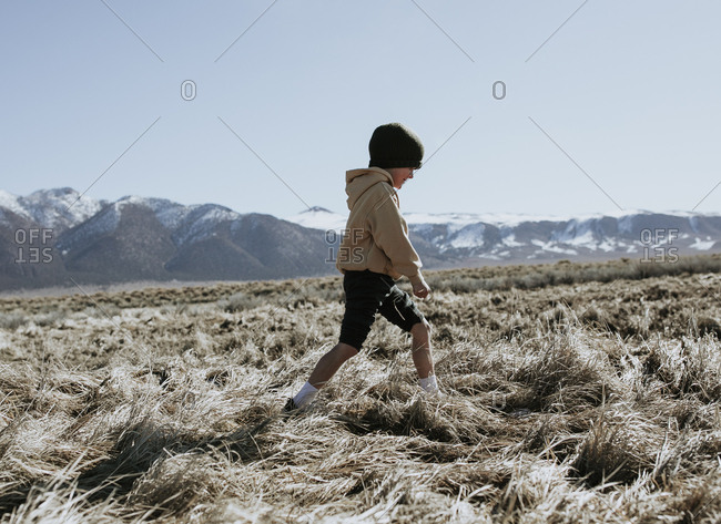 Young boy walking looking down with mountains in the background
