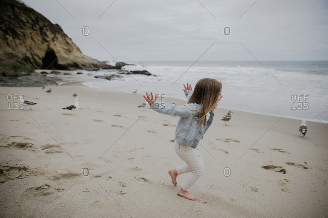 Young girl chasing seagulls at the beach