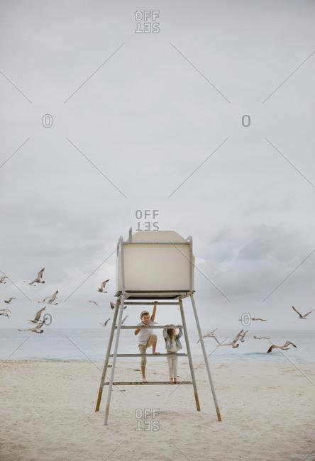 Two children climbing a lifeguard tower, Laguna Beach, California