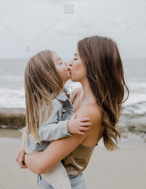 Mother and daughter kissing one another on beach