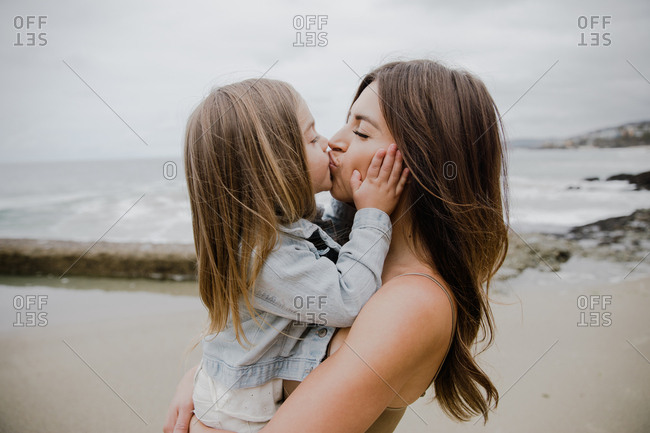 Daughter kissing mother on beach