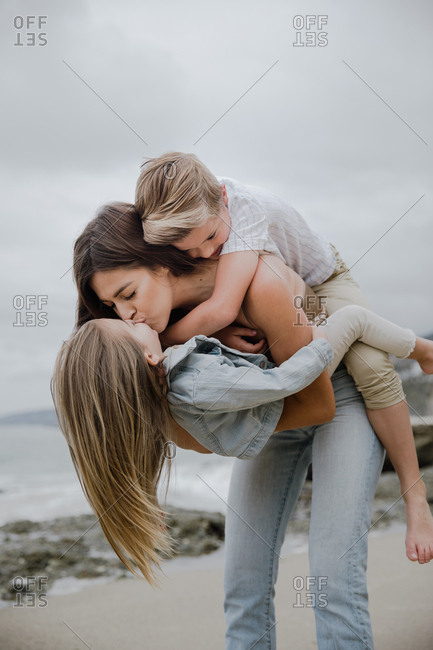 Mother holding both her kids kissing each other