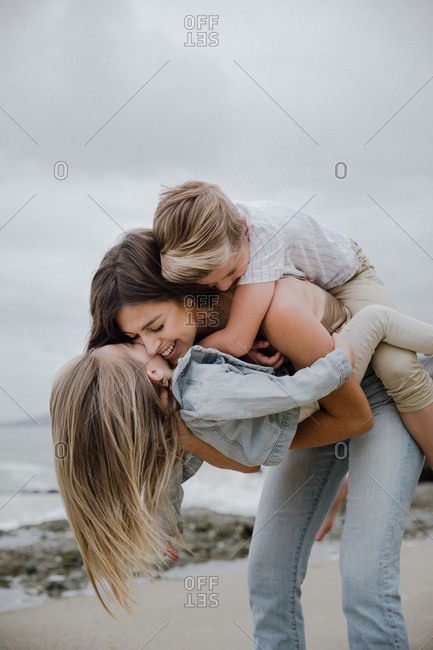 Mother holding both her kids kissing on beach