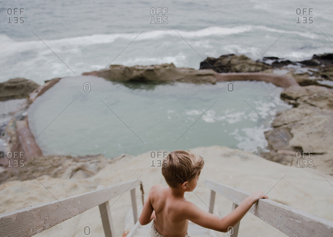 Young boy walking down steps to beach