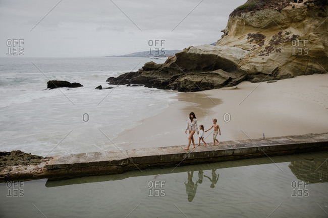 Mother exploring the beach with her children near a tide pool
