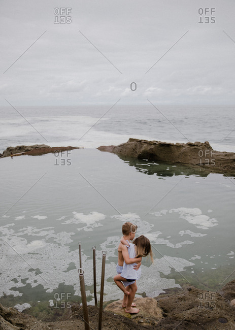 Siblings holding each other in a hug on the tide pool overlooking the ocean